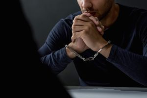 Criminal man with handcuffs in interrogation room feeling guilty after committed a crime.
